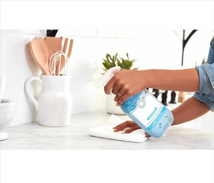 hand holding spray bottle cleaning countertop
